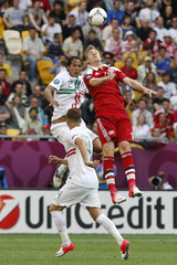 Portugal's Alves heads the ball with Denmark's Bendtner during their Group B Euro 2012 soccer match at the New Lviv stadium in Lviv