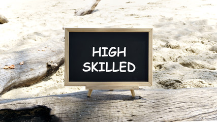 "Blackboard on a tree trunk with the words ""HIGH SKILLED"". Background beach sand.motivation concept."