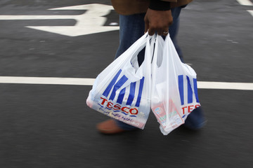 A man carries a carrier bag as he leaves a Tesco supermarket in Hendon in London