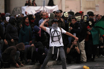 A protester throws a stone to police during clashes at 24-hour nationwide general strike in Lisbon