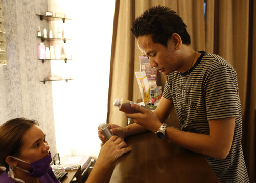 A man looks at skin care products after having a facial treatment at a clinic at a mall in Quezon City Metro Manila