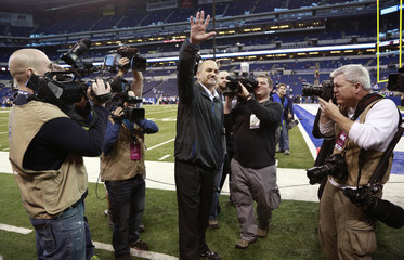 Colts coach Chuck Pagano waves while on the field before an NFL football game in Indianapolis, Indiana.