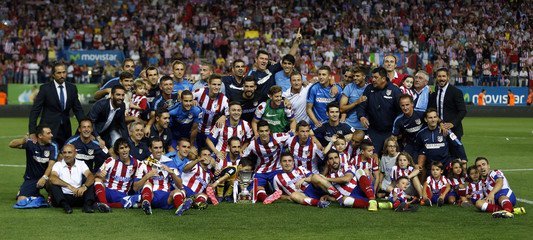 Atletico Madrid's team members pose with the trophy after winning the Spanish Super Cup second leg soccer match against Real Madrid in Madrid