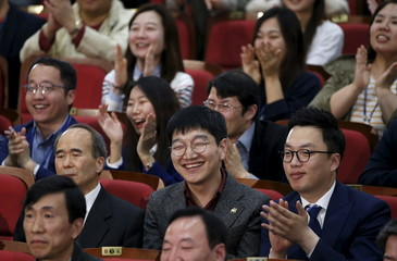 Members of the main opposition Minjoo Party of Korea, react as they watch a news report on results of exit polls in Seoul