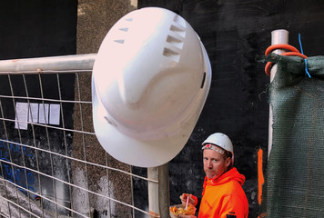 A worker eats his lunch behind a safety hat that rests on a fence at a construction site in central Sydney, Australia