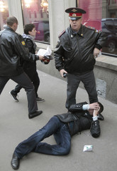 Police detain a gay rights activist during an unsanctioned protest in Moscow