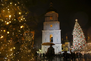 People walk past Christmas trees with Bell tower of Cathedral of St. Sophia seen on background in central Kiev