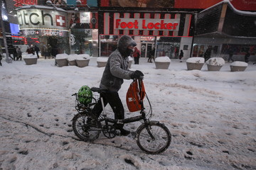 A man pushes his bicycle along 7th Avenue during a snow storm in Times Square in the Manhattan borough of New York