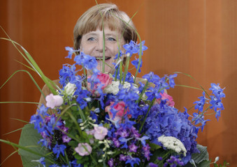 German Chancellor Merkel holds flowers she received for her 59th birthday before weekly cabinet meeting in Berlin