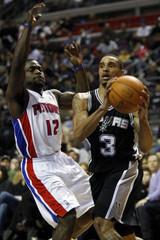 Spurs guard Hill drives past Pistons guard Bynum during the first half of their NBA game in Auburn Hills