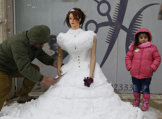 A hairdresser uses a knife to carve a snow sculpture in front of his shop in Basour village