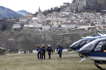 French gendarmes walk in a filed before an official ceremony near the crash site of an Airbus A320 in Seyne-les-Alpes