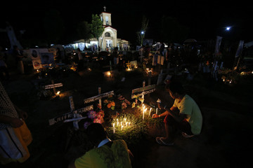 Typhoon survivors light candles for their family members and relatives who perished during the onslaught of Typhoon Haiyan in Palo