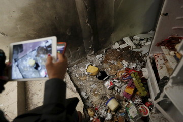 A journalist takes photographs of scattered food items in the kitchen at a safe house in Los Mochis