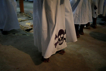 A voodoo believer dances in a dress decorated with a skull and crossbones during a celebration of Fet Gede in a Peristil, a voodoo temple, in Port-au-Prince