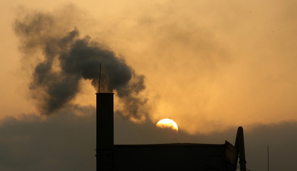 A sunset is seen in the background of a chimney of a concrete factory in Hanoi