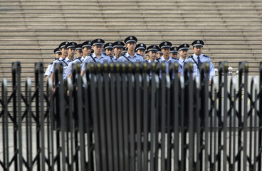 Policemen walk toward a fence in front of a court in Jinan