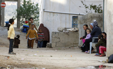 Palestinian women and children sit next to their homes in the West Bank village of Awarta