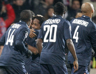 Makoun of Olympique Lyon celebrates with team mates after scoring against Real Madrid during their Champions League soccer match at the Gerland stadium