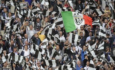 A Juventus supporter waves an Italian flag with the club's logo at their Italian Serie A soccer match against Palermo at the Juventus stadium in Turin