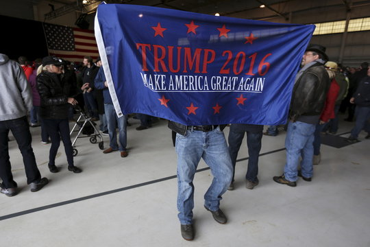 A supporter of U.S. Republican presidential candidate Trump holds up a banner as he waits for a campaign event to begin at an airplane hanger in Rochester, New York
