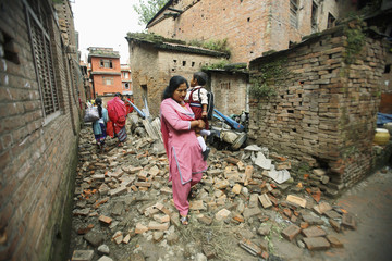 A resident, carring her child to school, walks past quake-damaged houses in Bhaktapur