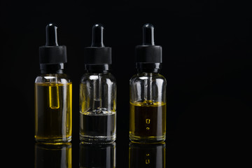 three liquid bottles for e cigarette on black background