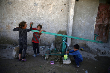 Children pull a lever as they wash up with water, in the rebel held besieged town of Douma, eastern Damascus suburb of Ghouta