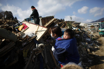 A family looks for their belongings amongst the debris of their destroyed house in Rikuzentakata