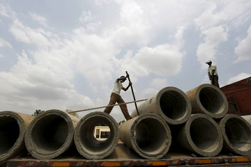Labourers unload cement sewer pipes from a trailer truck along a roadside on the outskirts of Ahmedabad