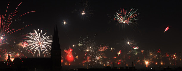 Fireworks explode over the spires of Familienkirche church and Vienna skyline during New Year celebrations