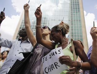 French citizen Saida cries next to her friends as they hold up pencils in a demonstration to show solidarity with the Unity March in Paris, and for the victims of the Paris terror attacks, in front of the French consulate in Sao Paulo