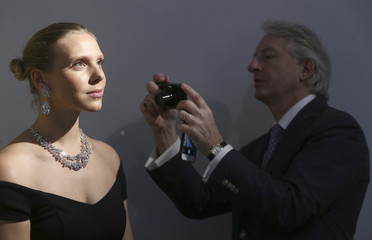 An assistant is photographed with Miroir de l'Amour, a pair of flawless diamond pear-shaped earrings and the diamond necklace Le Jardin d'Isabelle, at Christie's auction house in London