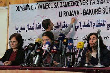 """A protester draws a heart around the word """"Li Rojava"""" protesting against its removal, while delegates take part in a conference in Syria's Kurdish-controlled northern regions, in the town of Rmeilan"""