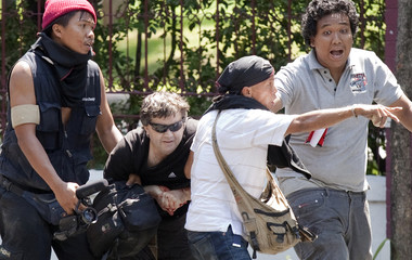 Anti-government 'red shirt' supporters assist Rand to safety after he was shot while covering clashes with army soldiers near Bangkok's Lumpini Park