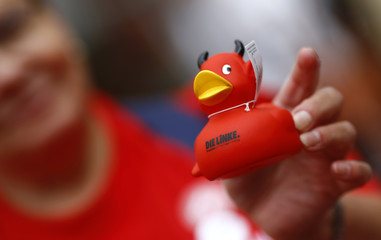 A supporter of Ramelow, top candidate of left wing party Die Linke purchases a red duck with devil's horns during a Thuringia state election campaign rally in Altenburg