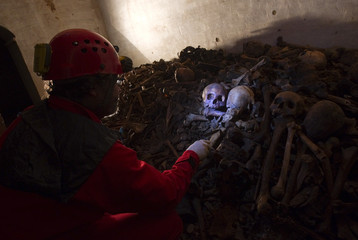 Italian speleologist Moretti looks at skulls inside a crypt in a new cemetery of Porto Ercole, in Tuscany
