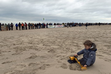 A child plays on the beach as people form a human chain during a march against climate change in Ostend