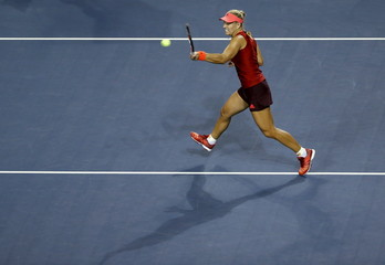 Kerber of Germany returns a shot to Wozniacki of Denmark during their Pan Pacific Open women's singles quarter-finals tennis match in Tokyo