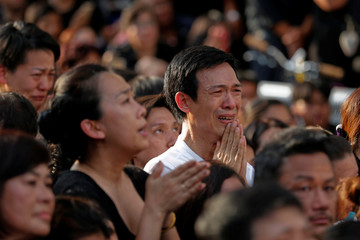People weep for Thailand's late King Bhumibol Adulyadej as they wait on the roadside while his body is moved from Siriraj hospital, where he died, to the Grand Palace, in Bangkok