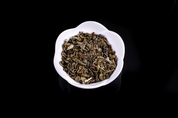 Green and black tea leaves in ceramic bowl on black background