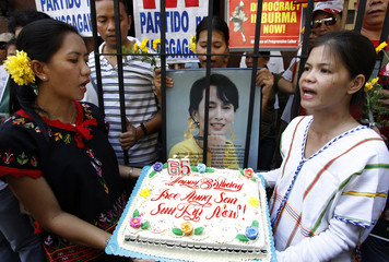 Filipino activists sing a birthday song while holding a cake during a protest outside Myanmar's embassy in Makati