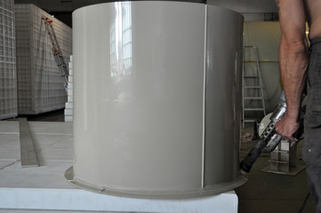 Male worker is sealing a cylindrical custom made plastic tank in the small manufacturing production