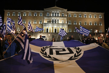 Supporters of Greece's far-right Golden Dawn party protest around a flag during a rally at central Syntagma square in Athens
