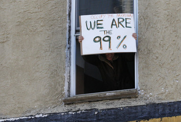 A woman holds a sign out of a window as the 2011 New York City Marathon goes by in New York