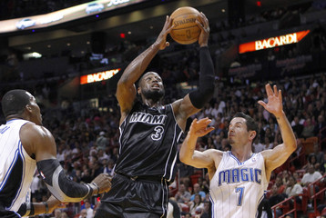 Heat's Wade moves between the Magic's Howard and Redick during their NBA basketball game in Miami