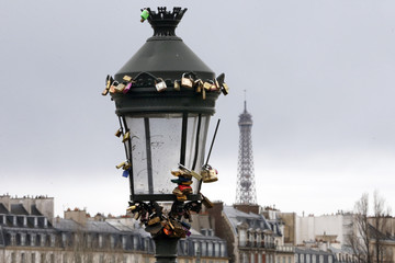 A view shows a street light covered with padlocks clipped by lovers on the Pont des Arts over the River Seine in Paris