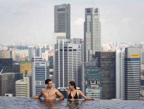 Models pose for photographers in the infinity pool of the Skypark that tops the Marina Bay Sands hotel towers in Singapore