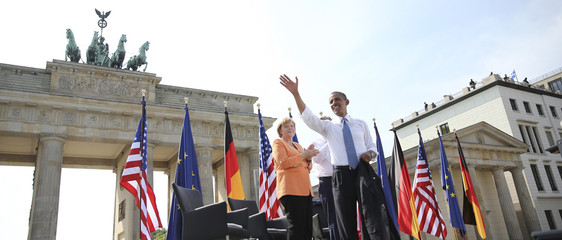 German Chancellor Merkel watches as U.S. President Obama waves after giving a speech in front of the Brandenburg Gate at Pariser Platz in Berlin
