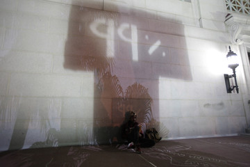 A man leans against the wall of City Hall at the Occupy LA encampment after the 12.01am eviction deadline in Los Angeles